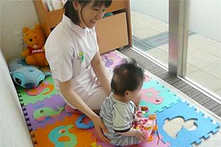 託児スタッフとキッズルームで遊ぶ乳児